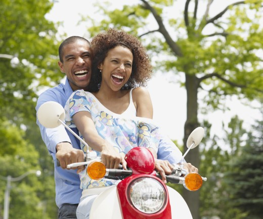 African American couple riding motor scooter